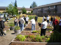 image of the outside of the everett community justice center with people near garden beds