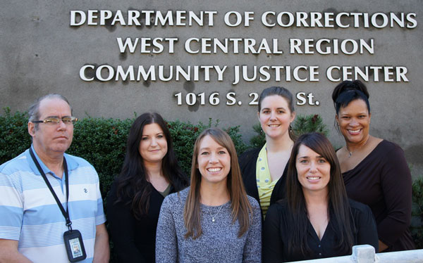 image of the outside of the Tacoma Community Justice Center with six staff members posing